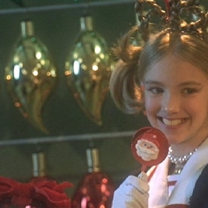 Young Martha May Whovier Smiling & Eating A Christmas Lollypop