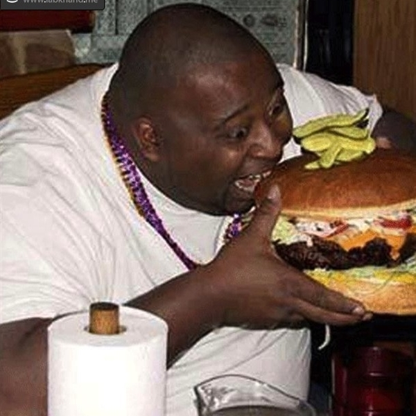 Fat black guy eating a cheeseburger