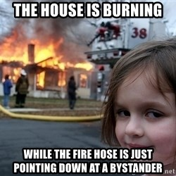 Disaster Girl - the house is burning while the fire hose is just pointing down at a bystander